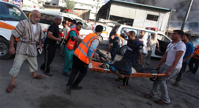 Varias personas tratan de socorrer a varias de las víctimas del ataque de Israel contra el mercado del barrio de Shayaía.