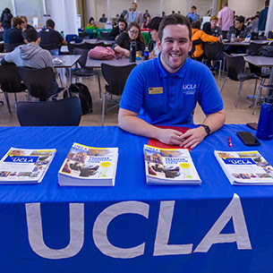 UCLA admissions representative sitting at a table talking to students