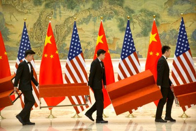 Aides set up platforms before a group photo with members of US and Chinese trade negotiation delegations at the Diaoyutai State Guesthouse in Beijing, China, 15 February 2019 (Photo: Mark Schiefelbein).