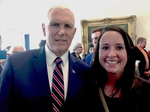 Sara Reed poses for a picture with Vice President Mike Pence in a crowded room in the White House.