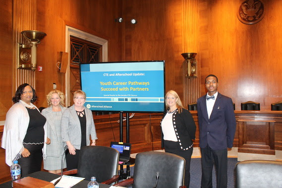 "Superintendent Balow stands with other presenters to the U.S. Senate Caucus in the congressional room where the meeting took place. A presentation screen reads, ""CTE and Afterschool Update: Youth Career Pathways Succeed with Partners."""