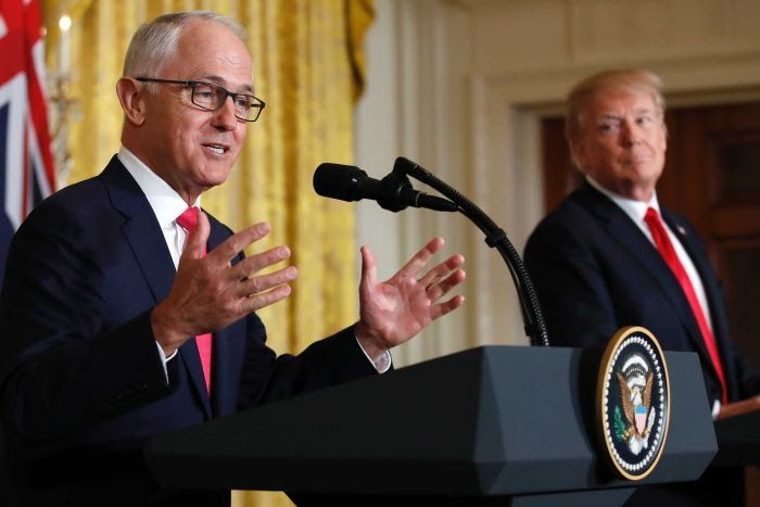 Donald Trump, in the background, gazes at Malcolm Turnbull as he speaks at a podium with his hands gesturing