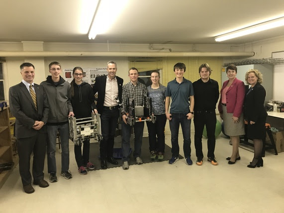 State Treasurer Mark Gordon, Secretary of State Ed Murray, State Auditor Cynthia Cloud, and State Superintendent Jillian Balow stand with high school students holding their robots.