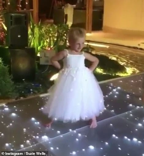 Playful: The sweet youngster looked adorable in her white bridesmaid's dress as she showcased her best moves in the clip
