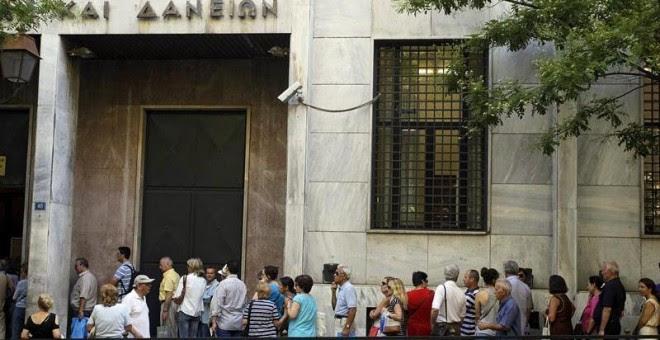 Un grupo de personas hace cola para realizar sus transacciones en el Fondo de Depósitos y Préstamos en Atenas. EFE/Orestis Panagiotou