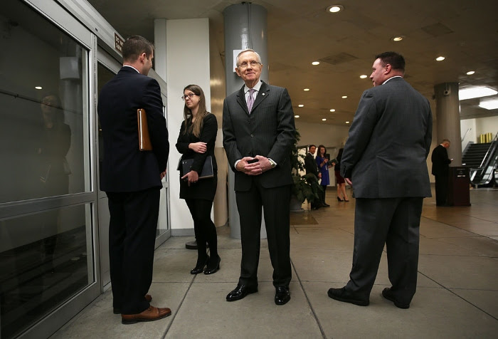 Then-Senate Majority Leader Harry Reid waits for the Senate subway after a vote in December 2013 on Capitol Hill.