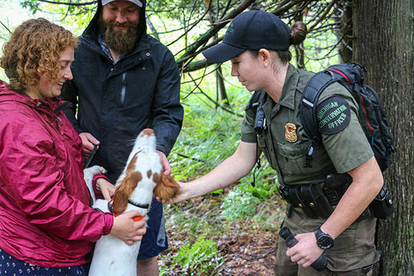 Michigan Conservation Officer Amanda McCurdy meets two people and their dog who were walking a trail.