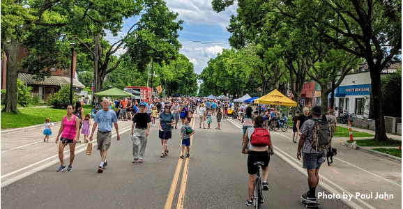 Folks walking on a bustling Minnehaha Ave at Open Streets Lake + Minnehaha