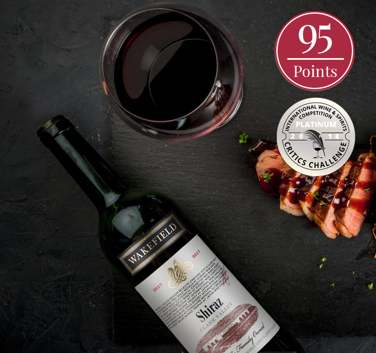 """Bottle and glass of Heritage Shiraz Clare Valley by Wakefield Wines 2017  """"95 Points"""" and """"Critics Challenge"""" seals"""
