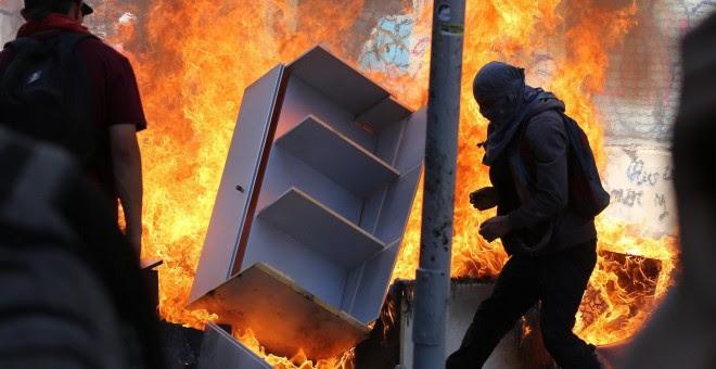 22-10-19 / Varios encapuchados montan barricadas frente a la policía tras manifestarse este martes en el centro de Santiago (Chile).  EFE/Elvis González