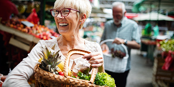 Woman at market with basket of veges