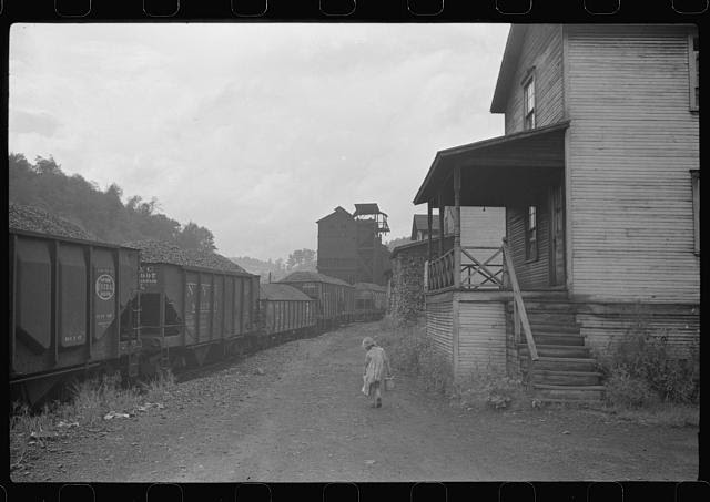 Coal miner's child taking home kerosene for lamps. Company houses, coal tipple in background. Pursglove, Scotts Run, West Virginia