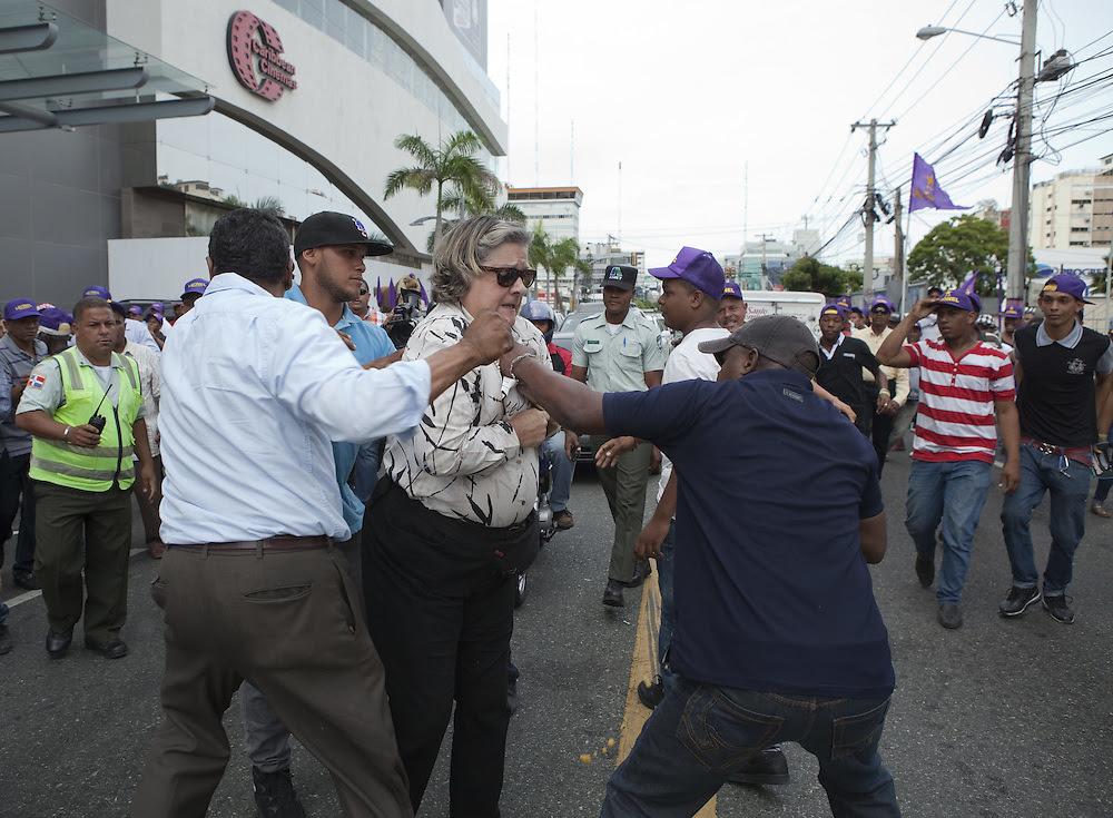 Jeanne Marie Delgado se enfrenta a cuatro lúmpenes ante la mirada indiferentes de agentes policiales. Foto: EFE