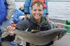 Academy participant poses with lake trout netted on Higgins Lake.