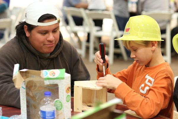 Student works with a student building a birdhouse.