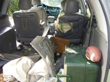 view of inside a car from the back hatch with damaged seats and equipment from a bear