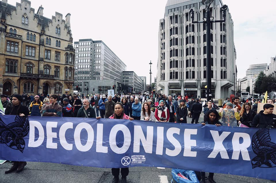 3 rebels blocking a road whilst holding a large blue banner which reads 'Decolonise XR'.