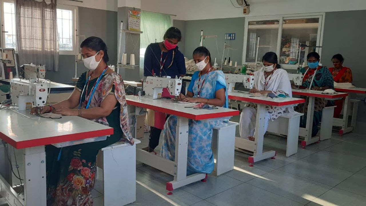 artisans wearing face masks, shown working in sewing centre