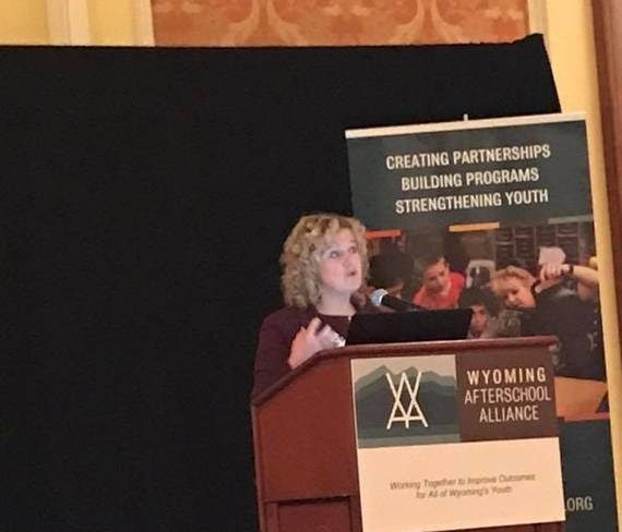 "State Superintendent Jillian Balow stands at the podium speaking at the Wyoming Afterschool Alliance conference. A banner behind her reads, ""Creating Partnerships, Building Programs, Strengthening Youth."""