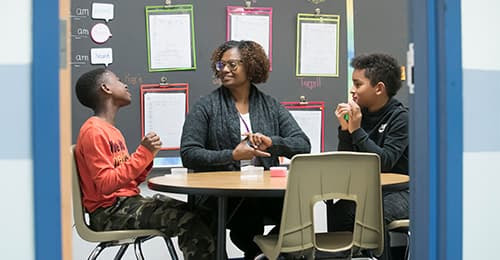 Clara Hendrick meets with two male students.