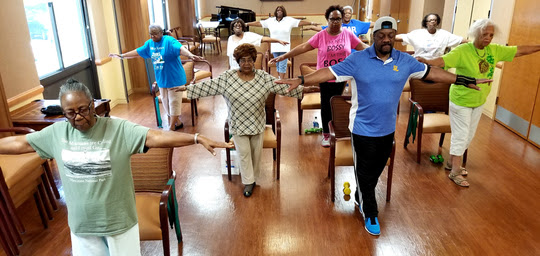 Group of seniors with arms stretch out doing falls prevention exercise