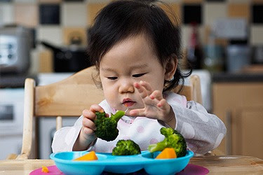 baby in high chair with veggies