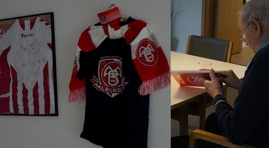 Væg med AAB-fodboldtrøjer og beboer, der kigger i bog om AAB.