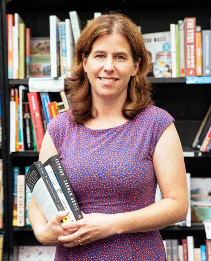 A white woman with shoulder-length brown hair, wearing a purple dress, holding a stack of books in front of a book shelf and smiling at the camera.