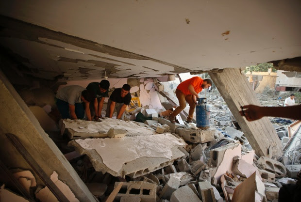 People search for their belongings in the rubble of a house destroyed in the northern Gaza Strip.