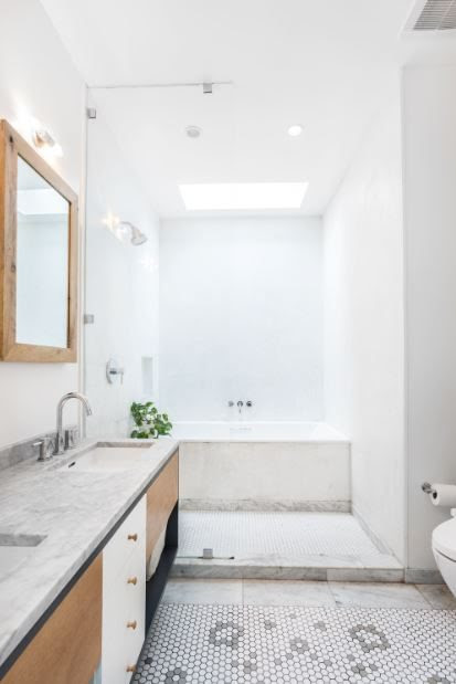 bathroom with skylight and double sink