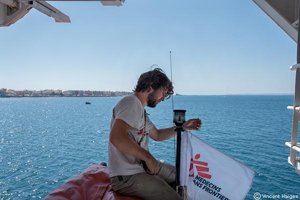 Matthijs, miembro del equipo, coloca una bandera de MSF a la lancha del Geo Barents.