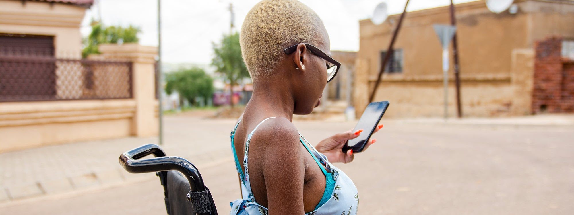 A black woman with short hair sits in a wheelchair and looks at her phone