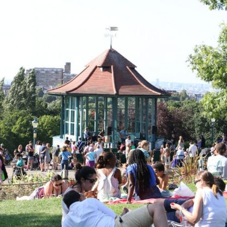 Groups of people relaxing on the grass in the sunshine at a concert on the Horniman Bandstand.