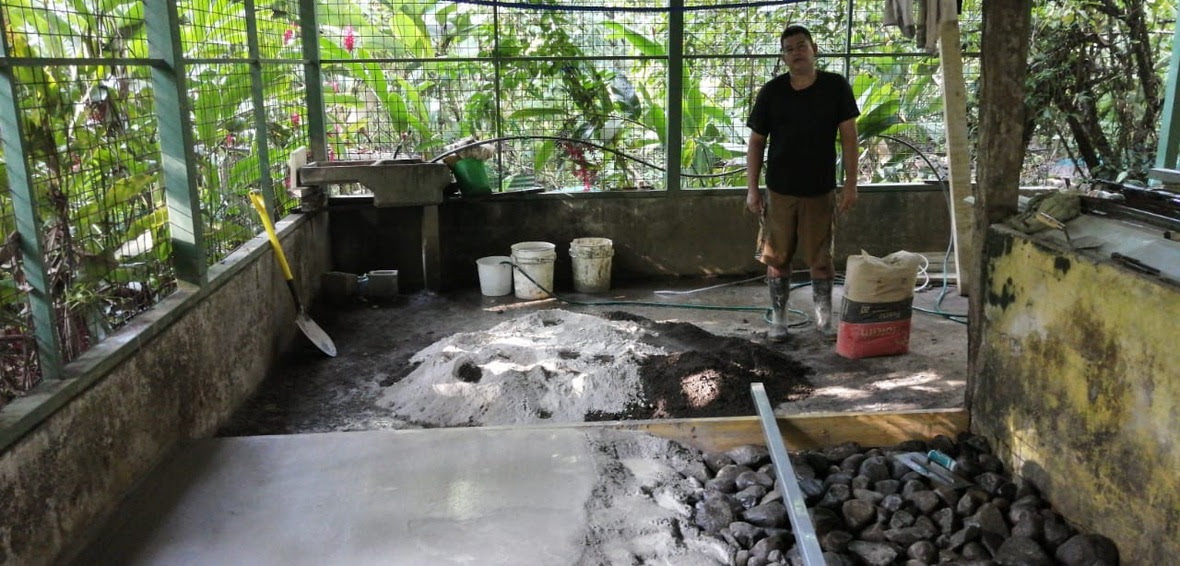 A worker stands behind a half-finished concrete floor with jungle in the background