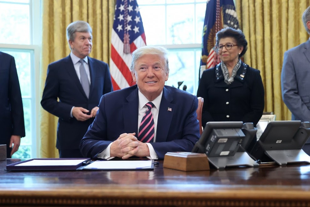 El presidente de los Estados Unidos, Donald Trump, sonríe, flanqueado por el secretario del Tesoro Steven Mnuchin, el senador Roy Blunt, la reponsable de la Oficina para las Pequeñas Empresas, Jovita Carranza y el líder de la minoría de la Cámara Kevin Mc