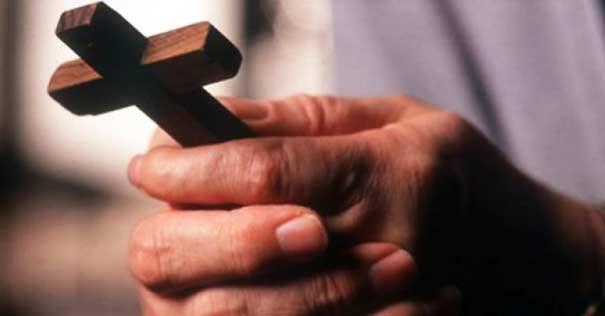 cruz madera marron sostenida en dos manos hombres