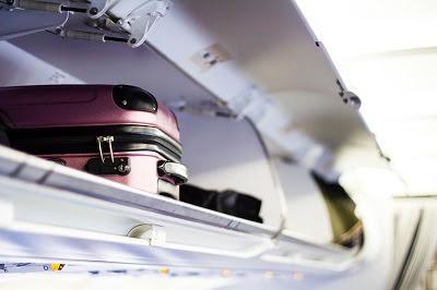 luggage in bin on plane