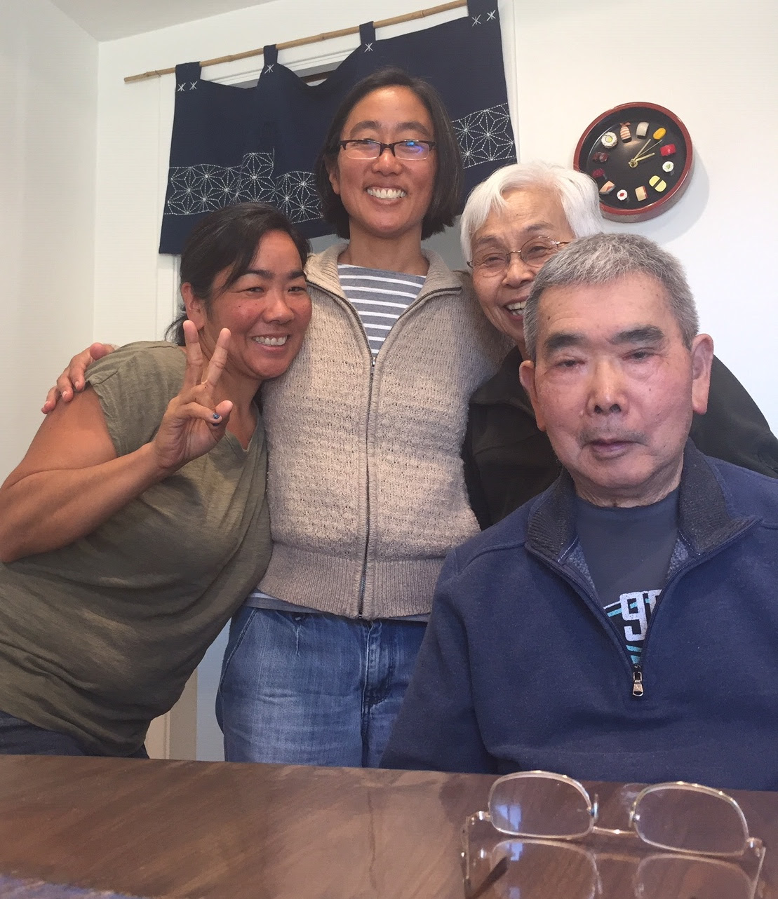 Three women embracing next to and behind an older man who is seated at the table in front of a pair of glasses, all smiling.
