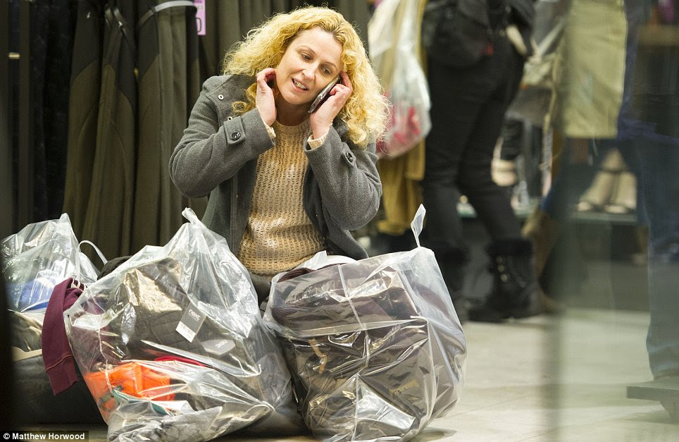 Laden: A woman at the Next branch in Cardiff surrounding by her Boxing Day bargains
