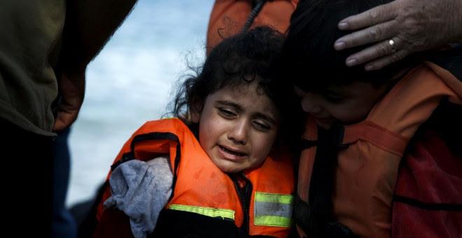 Una niña siria refugiada es abrazada por su hermano mientras llora, momentos después de llegar a un bote en la isla griega de Lesbos. REUTERS