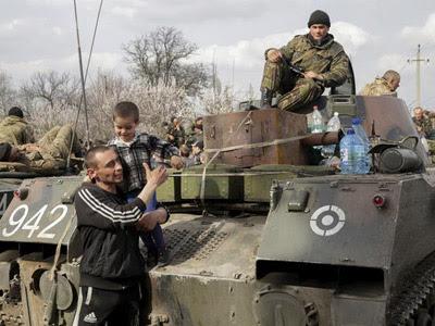 Un hombre y su hijo, junto a soldados ucranianos en un vehículo de combate que toma posiciones en la región de Donetsk, Ucrania, el 16 de abril del 2014. EFE/Anastasia Vlasova