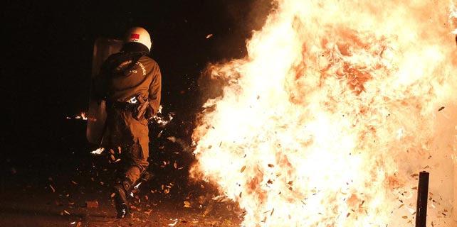 Un antidisturbios esquiva un cóctel molotov durante los enfrentamientos de la noche del sábado en Atenas. REUTERS/Alkis Konstantinidis