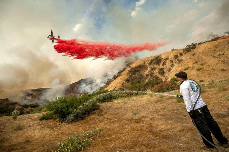 Aaron Funk waters the hillside behind his parents' home as a plane drops water north of Los Angeles over the weekend to fight what's become the largest fire in the city's history. (Paul Rodriguez/Orange County Register/AP)