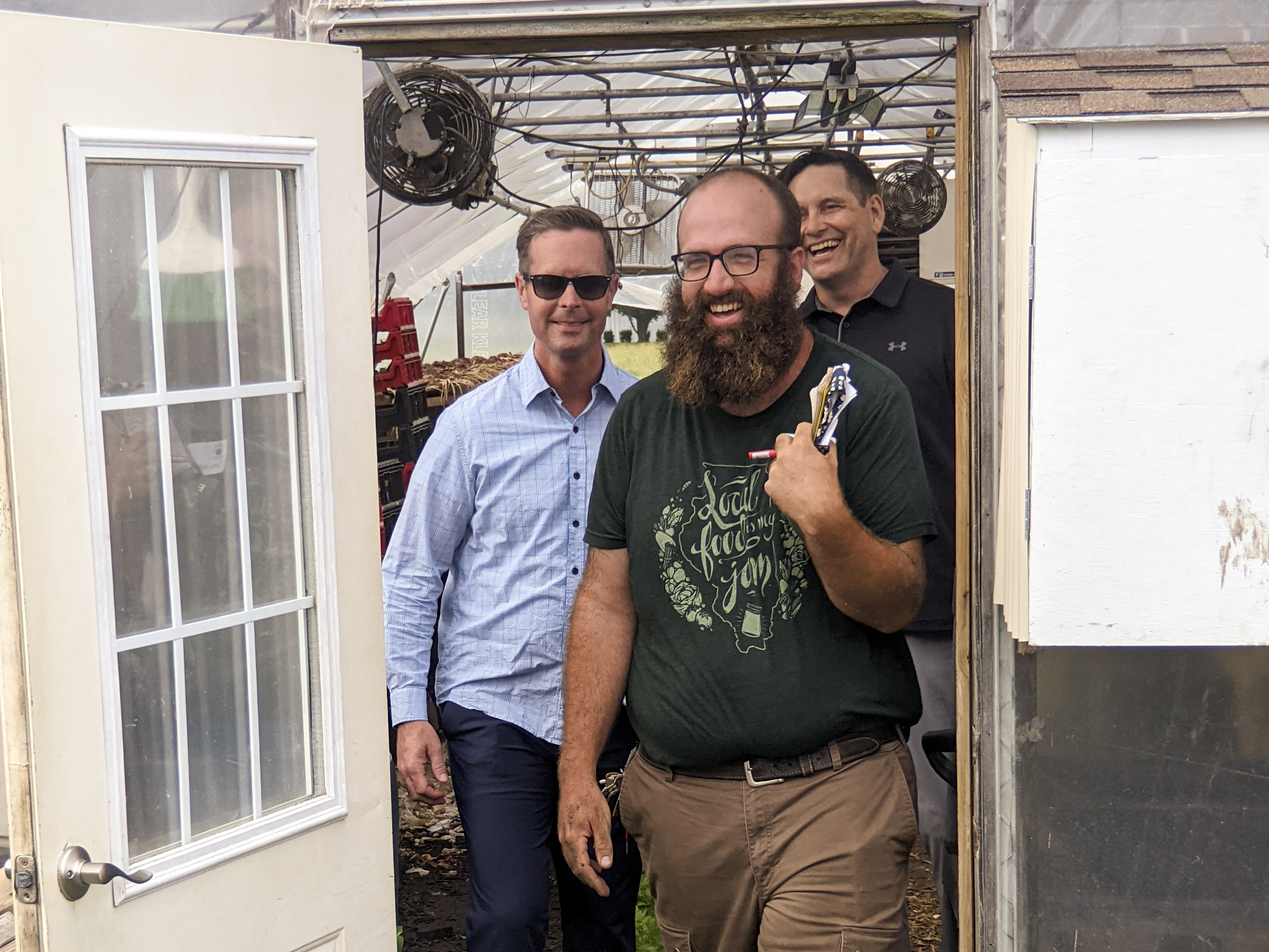 Congressman Rep. Rodney Davis, State Rep. Tim Butler and John Williams, farm manager of Sola Gratia exit a green house smiling and laughing.