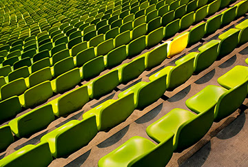 Rows of green seats with one yellow seat