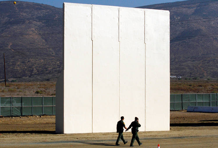 U.S. border patrol officers walk near a prototype for Trump's border wall. (Jorge Duenes/Reuters)