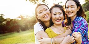 Asian Daughters Hugging Mom; Smiling
