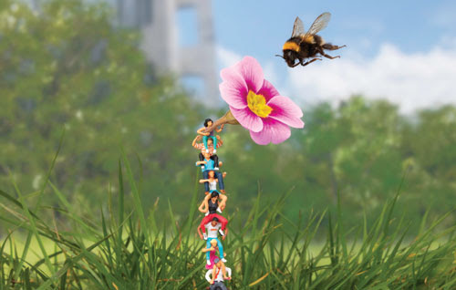 A tower of people work together to help a bee (c) Slinkachu (2020)