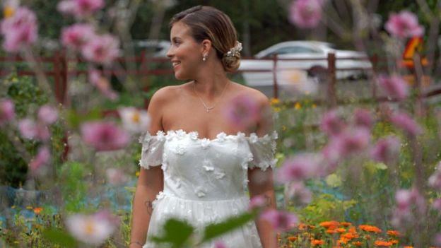 Nicole Falciani posa para foto com roupa de gala e em meio a flores