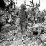 Photo prise en avril 1945 : des marines américains traversent un village à Okinawa, Japan, où des soldats nippons gisent sur le bord du chemin après la sanglante bataille sur l'île. (Crédits : AFP PHOTO/THE NATIONAL ARCHIVES/NORRIS G. MCELROY)